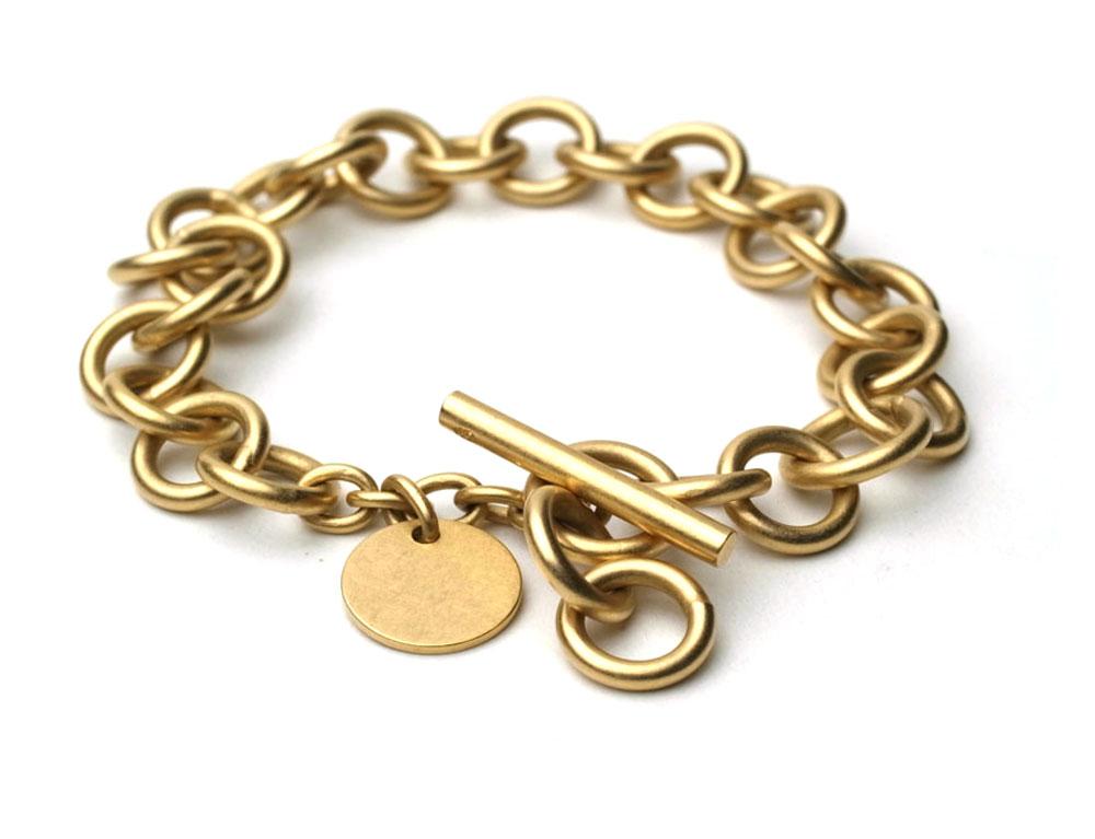 Armkette aus runden Gliedern mit Knebelverschluss und angehängter Ronde, gelbgoldplattiert